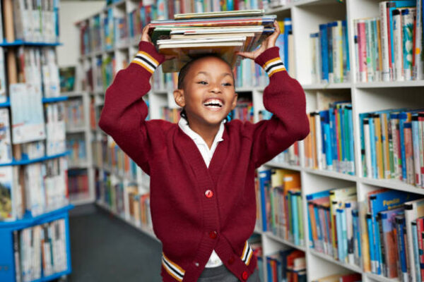Boy holding lots of books in a library