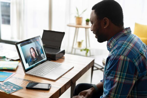 Man sitting with laptop talking with video conferencing