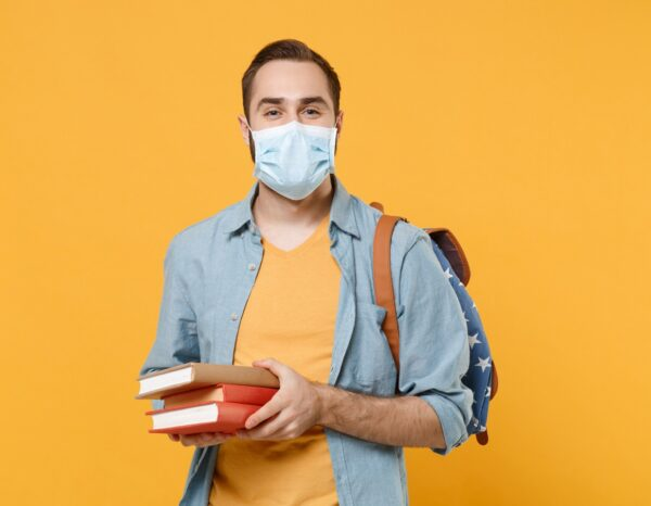 Man in mask holding books