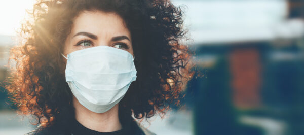 Lovely curly haired caucasian lady protecting herself from viruses while wearing special mask