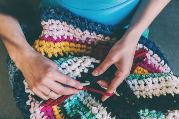 The woman is crocheting.