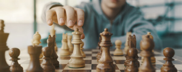 Boy playing chess and moving a piece, hand close up