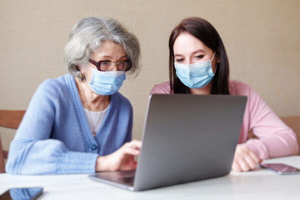 An elderly woman and a young woman wearing masks on her face use a laptop
